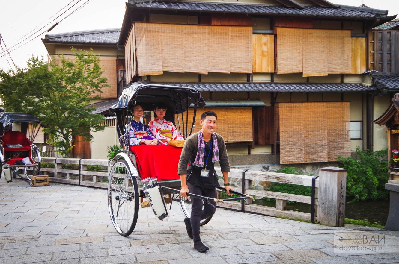 рикшя тянет повозку с гейшами в киото гион